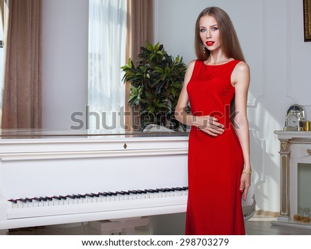 Beautiful brunette woman in a red dress. Studio shot. Long hair. Red lips. - stock photo
