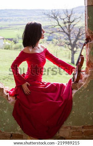 Beautiful, brunette woman in an old, abandoned house, wearing a red dress, looking sad and melancholic  - stock photo
