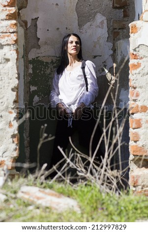 Beautiful, brunette woman in an old, abandoned house, wearing a white blouse, looking sad, scared and melancholic  - stock photo
