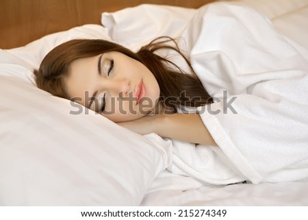 beautiful brunette woman in bed - stock photo