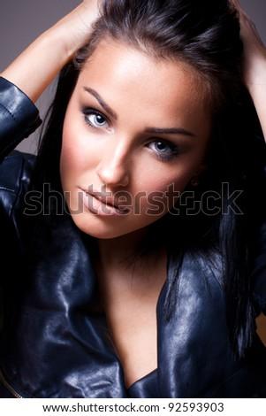 Beautiful brunette woman in black jacket - stock photo