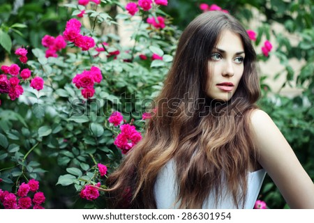 Beautiful brunette woman in blooming rose flowers. Outdoor portrait. Woman in spring park