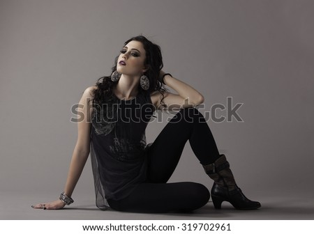Beautiful brunette woman in edgy clothing wearing dramatic makeup - stock photo