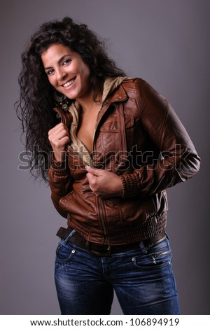 beautiful brunette woman in leather jacket and jeans studio portrait - stock photo
