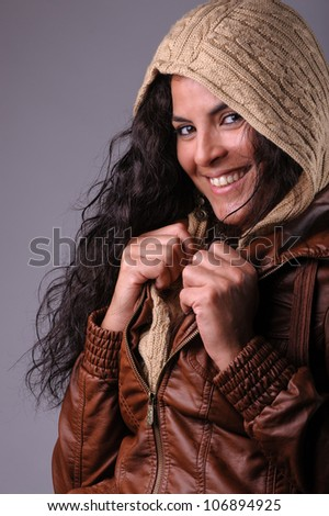 beautiful brunette woman in leather jacket and wool sweater with hood - stock photo