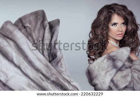 Beautiful brunette woman in mink fur coat. Fashion Beauty girl model with long healthy wavy hair styling. - stock photo