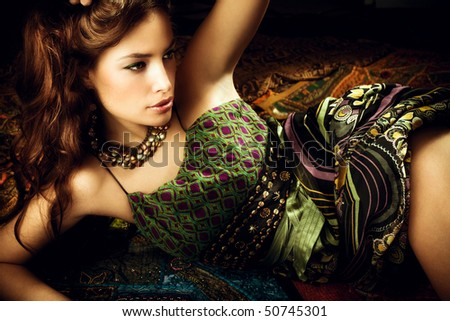 beautiful brunette woman in oriental style clothes, studio shot - stock photo