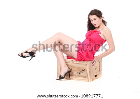 Beautiful brunette woman in sexy pink dress and black high heel stillettos sitting on wooden box crate seductively