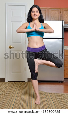 Beautiful brunette woman in sports bra and athletic pants performing yoga pose as she works out in studio apartment - fitness