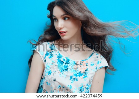 Beautiful brunette woman in summer dress over blue background - stock photo