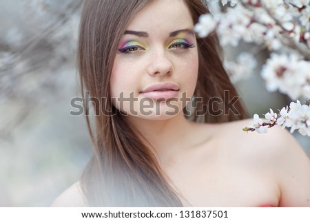 beautiful brunette woman in the park on a warm spring day - stock photo