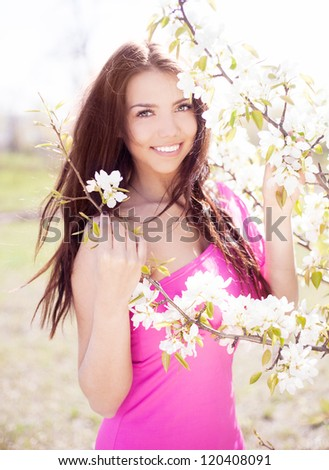 beautiful brunette woman in the park standing near the apple tree on a warm summer day - stock photo