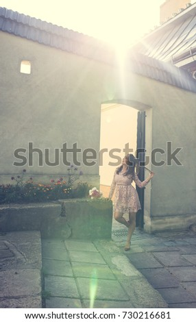 Beautiful brunette woman in trendy dress posing at the wall in rays of sun. Vintage toning