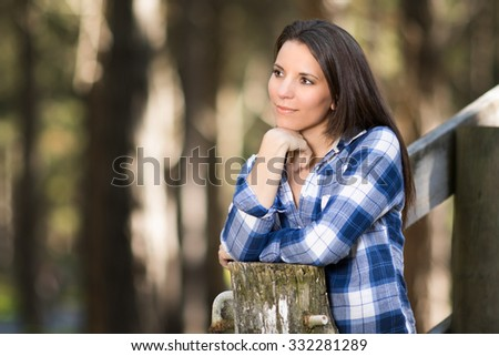 Beautiful brunette woman leaning on fence - stock photo