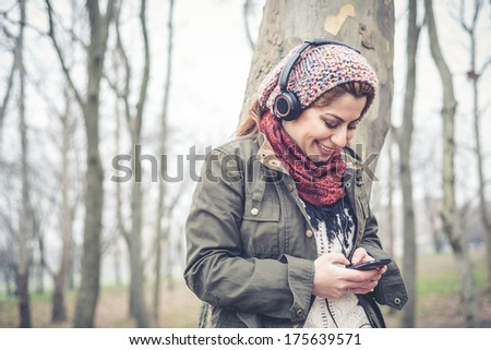 beautiful brunette woman listening to music with headphones at the park outdoor in winter