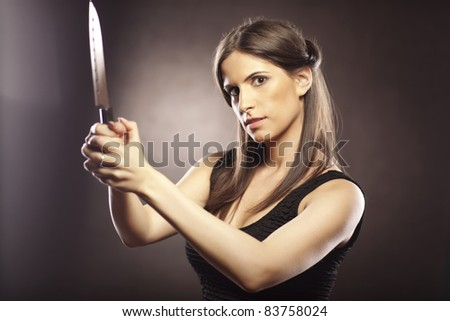 Beautiful brunette woman looks threatening with a knife in her hands. She is dressed in a black dress on a dark brown background. - stock photo