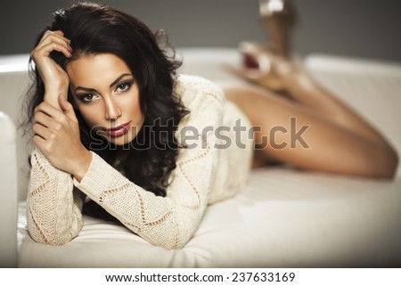Beautiful brunette woman lying on the bed and smiling  - stock photo