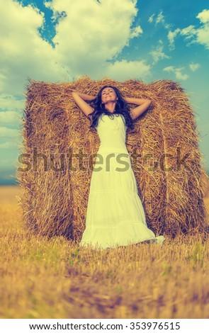 Beautiful brunette woman near hay bale in warm summer day - stock photo