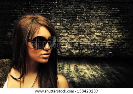 Beautiful brunette woman on brick wall - stock photo