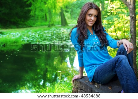 Beautiful brunette woman outdoor near forest lake