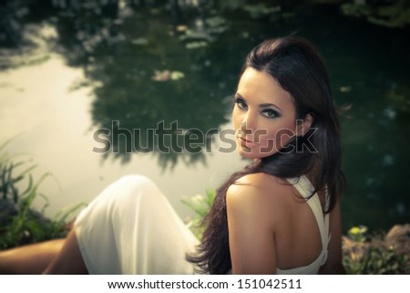 beautiful brunette woman outdoor portrait by the pond - stock photo