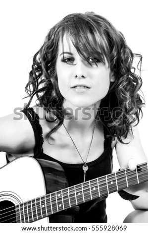 Beautiful brunette woman playing an acoustic guitar while singing a folk song.
