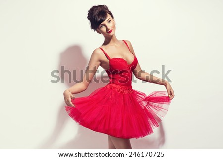 Beautiful brunette woman posing in red dress. Valentines day - stock photo