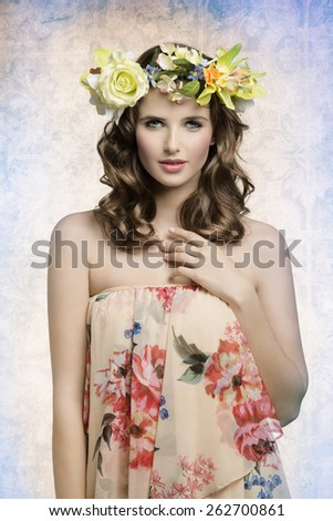 beautiful brunette woman posing in spring shoot with some flowers on the head and floral dress, natural make-up and hair-style. looking in camera with sensual expression  - stock photo