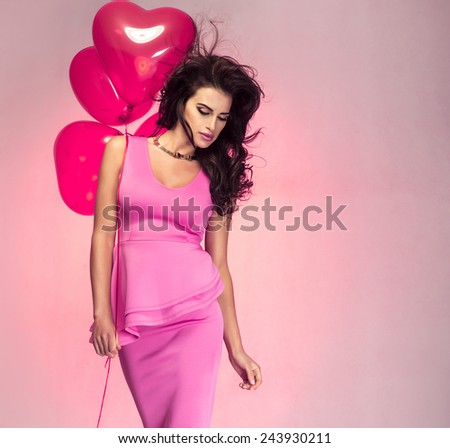 Beautiful brunette woman posing with heart balloons. St. Valentine's day. - stock photo