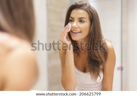 Beautiful brunette woman removing makeup from her face - stock photo