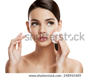 Beautiful brunette woman removing makeup from her face, skin care concept / photo composition of brunette girl  - isolated on white background  - stock photo