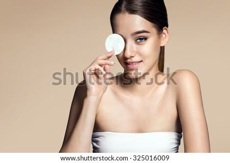 Beautiful brunette woman removing makeup from her face, skin care concept / photoset of attractive brunette girl  - stock photo