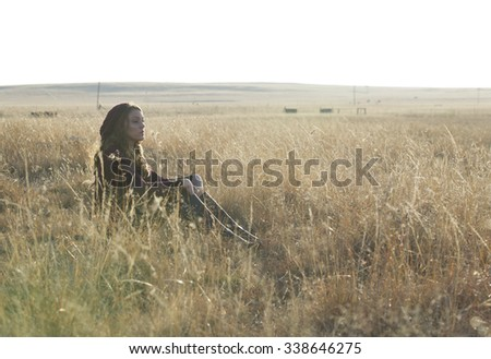 Beautiful brunette woman seated in a field of grass in the early morning sunshine