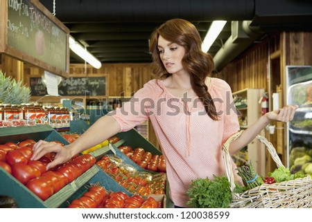 Beautiful brunette woman shopping for tomatoes in supermarket - stock photo