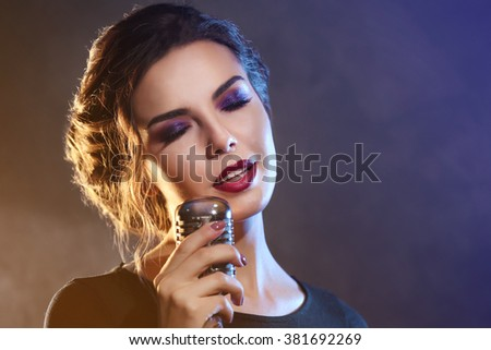 Beautiful brunette woman singing on grey background