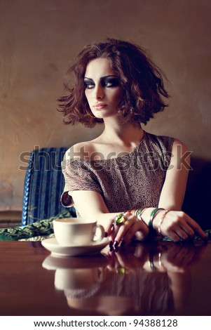 Beautiful brunette woman sitting alone in a restaurant with a cup of coffee - stock photo