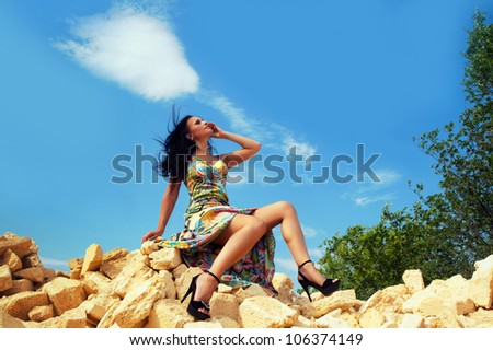 Beautiful brunette woman sitting at the yellow bricks - stock photo