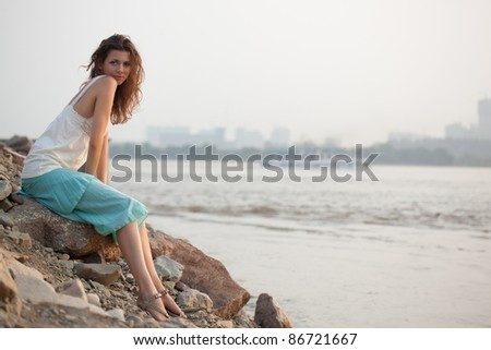 beautiful brunette  woman sitting near water - stock photo