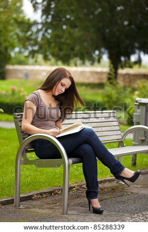 beautiful brunette woman sitting on a bench in a park and reading a book - stock photo