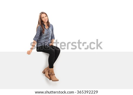 Beautiful brunette woman sitting on a blank white signboard and looking at the camera isolated on white background - stock photo