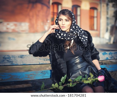 Beautiful brunette woman sitting outside in urban scene. Fashionable female with head scarf with a rose on her knees - outdoor shot. Woman in black sitting on a bench in the city - stock photo