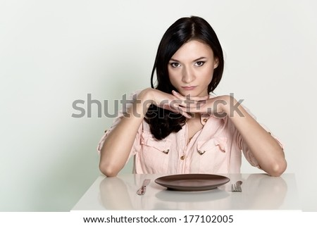 Beautiful brunette woman sitting with an empty plate and wait her lunch. White background - stock photo