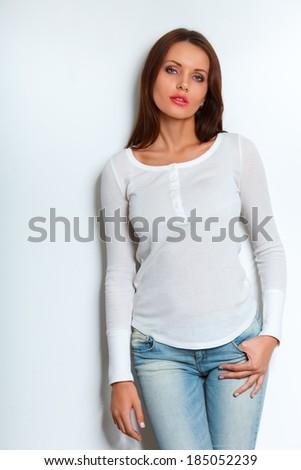beautiful brunette woman standing near white wall - stock photo