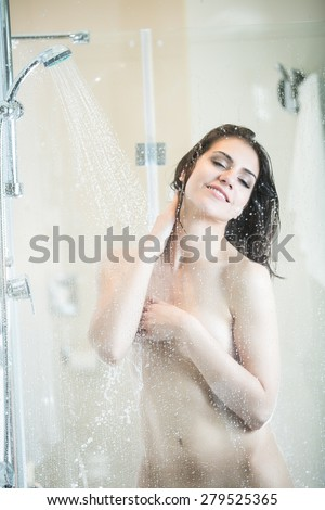 Beautiful brunette woman taking shower after long stressful day.Woman showering and enjoying bath.Using douche shower gel,body lotion,shower relaxing muscles.Depilation and anti cellulite treatment. - stock photo