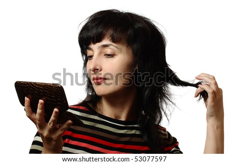 Beautiful brunette woman twists her hair as she admires herself in portable mirror, isolated on white - stock photo