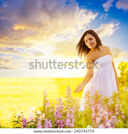 beautiful brunette woman walking in a field at sunset and touching flowers - stock photo