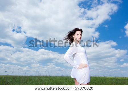 Beautiful brunette woman walking on field enjoying wind wave - stock photo