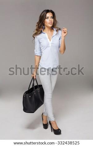 Beautiful brunette woman walking on studio background with bag - stock photo