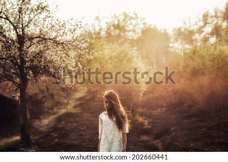 beautiful brunette woman walking outdoors, dramatic theme, spring ground and trees - stock photo
