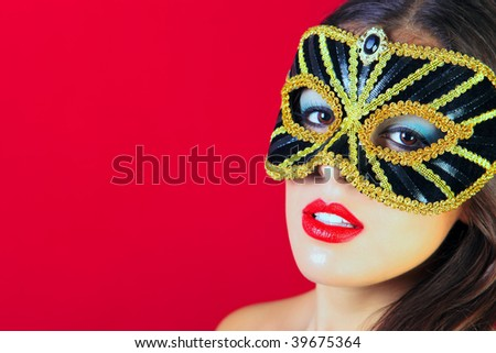 Beautiful brunette woman wearing a black and gold masquerade mask and bright red lipstick against a red background. - stock photo